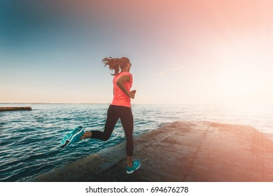 healthy lifestyle young woman runner running on seaside. Motion shot