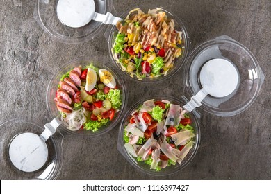 Healthy light vegetarian salad or hearty with meat in plastic package for take away or food delivery.  Outdoor food in plastic containers. Solution of balanced nutrition.