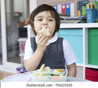 Healthy little boy his eating packed lunch, Cute school kid having lunch with star shape bread toast with honey, fruit salad and fish in lunch box, Healthy food for Children at school