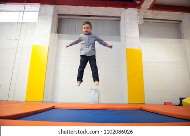 healthy little boy jumping on trampoline indoors in sport centre