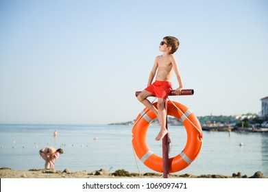 healthy little boy in sunglasses sits on pole with orange lifebuoy hanging on it on summer beach with people in baywatch