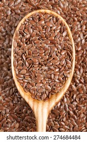 Healthy little brown flax seeds super foods  in wooden spoon. Organic vegetarian super food.