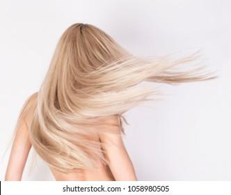 Gesunde, lange platinblonde Haare in Bewegung. Anonymer Look von hinten.