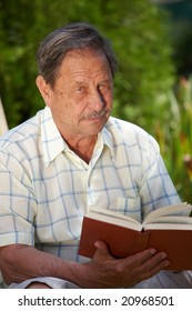 Healthy looking old man is his late 70s sitting in garden at home and reading book.