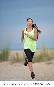 Healthy Looking Young Woman Jogging under Morning Blue Sky by Beach
