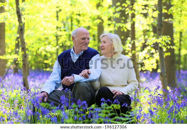 Healthy loving senior couple relaxing in beautiful summer forest full of fresh blooming bluebells or wild blue hyacinth flowers - active retirement concept