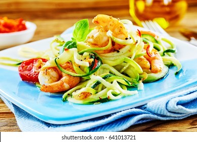 Healthy low carbohydrate seafood starter with a fresh raw vegetable salad and grilled spicy queen prawn tails dressed in olive oil served on a blue platter