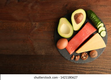 Healthy low carbs products on slate blackboard on wooden background. Concept ketogenic diet, healthy food. Top view, copy space.