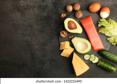 Healthy low carbs products on slate blackboard on black background. Concept ketogenic diet, healthy food. Top view, copy space.