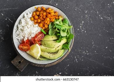 Healthy lunch bowl: basmati rice, chickpeas in tomato sauce, avocado, cherry tomatoes, corn salad