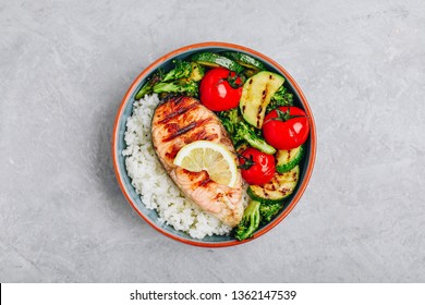 Healthy lunch bowl with grilled salmon, rice and vegetables. Grilled zucchini, broccoli and tomato with salmon steak and rice.
