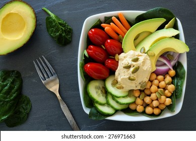 Healthy lunch bowl with super-foods and fresh mixed vegetables, overhead scene on dark slate
