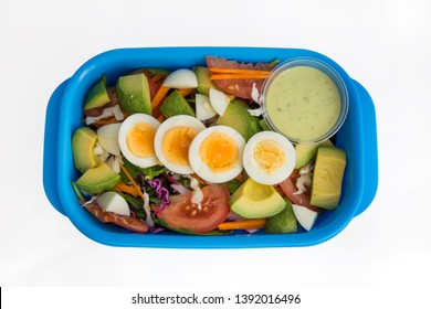 Healthy lunch box with avocado and egg and avocado yogurt dressing