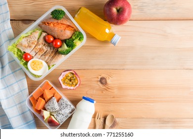 Healthy lunch box in plastic package, Grilled chicken breast with sweet potato, egg and vegetable salad, fruit, orange juice, milk. Diet food concept. Top view and Copy space.
