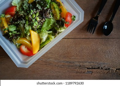 Healthy lunch box preparation : Mango avocado quinoa salad with tomatoes and edamame beans in bioplastic take out packaging or to go container on wooden background with black plastic fork and spoon.