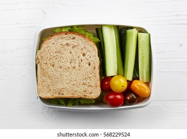 Healthy lunch box with sandwich and fresh vegetables on white wooden background. From top view