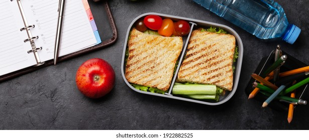 Healthy lunch box with sandwich and vegetables, apple and water bottle on office table. Top view flat lay