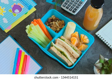 Healthy lunch box for school with sandwich, vegetablea, nuts and fruits