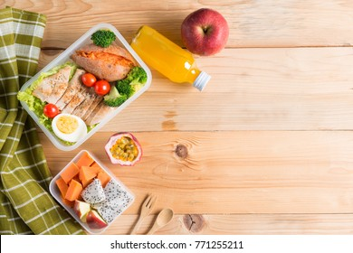 Healthy lunch boxes in plastic package, Grilled chicken breast with sweet potato, egg and vegetable salad, fruit, orange juice. Diet food concept. Top view and Copy space.