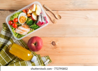 Healthy lunch boxes in plastic package, Grilled chicken breast with vegetable salad, egg and fruit, orange juice, red apple. Diet food concept. Top view and Copy space.
