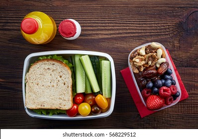 Healthy lunch boxes with sandwich, fresh vegetables, fruits and nuts on wooden background. From top view