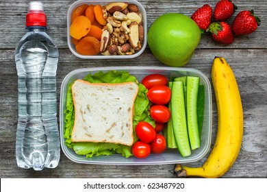 Healthy lunch boxes with sandwich and fresh vegetables, bottle of water, nuts and fruits on rustic wooden background. top view