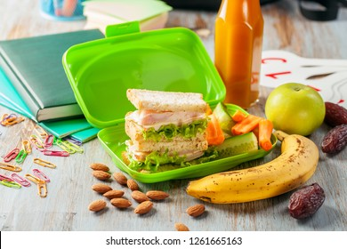 Healthy lunch in a container and school stationery on a wooden background. School concept.