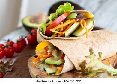 A healthy lunch or dinner of a vegan / vegetarian wrap made with  argula lettuce, sliced tomatoes, cucumbers, avocado, bell peppers and carrots. Selective focus on sandwich on top.