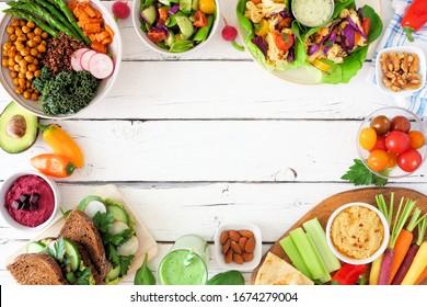 Cadre de repas sain pour le déjeuner. Scène de table avec bol de Bouddha nourrissant, salade, enveloppement de laitue, légumes et sandwichs. Vue de dessus sur fond blanc bois. Copier l'espace.