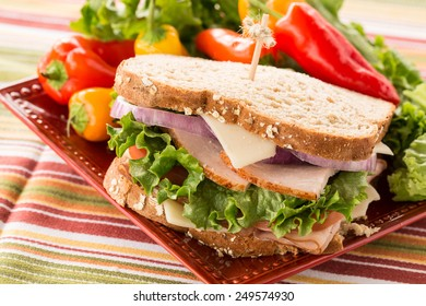 Healthy lunch food sandwich with turkey and ham on a plate with sweet peppers and lettuce