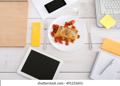 Healthy lunch in office, selective focus on steamed fat free lasagna dish at desk. Restaurant food on office table with mobile phone, papers and tablet at background. Diet meals concept, top view