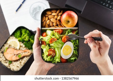 Healthy lunch at office workplace. Man eating nutrition lunch from takeaway lunch box at working table with laptop. - Shutterstock ID 1382567966