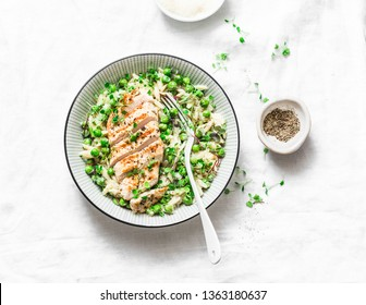 Healthy lunch -  orzo, green peas, spring herbs risotto and grilled chicken breast on a light background, top view