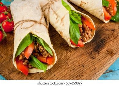 Healthy lunch snack. Sandwiches twisted roll Tortilla with beef and vegetables a wooden cutting board on blue wooden rustic table, copy space, top view