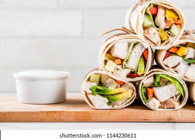 Healthy lunch snack. Stack of mexican street food fajita tortilla wraps with grilled buffalo chicken fillet and fresh vegetables, light grey background copy space