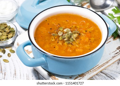 healthy lunch. spicy pumpkin soup with lentils in a saucepan, closeup top view
