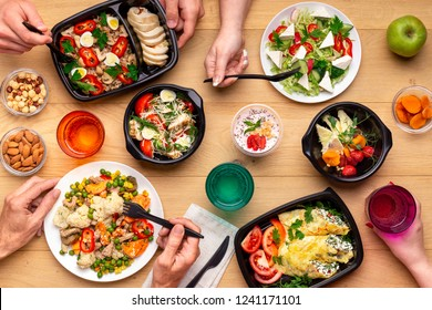 Healthy lunch time at office workplace. Four people eating healthy meals from take away lunch boxes and plates at wooden table. concept, top view