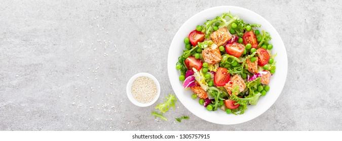 Gesunder Gemüsesalat mit gebackenem Lachsfisch, frisch grüner Erbse, Salat und Tomate. Draufsicht