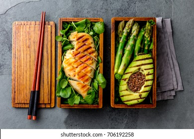Healthy lunch in wooden japanese bento box. Balanced healthy food grilled chucken and avocado with asparagus and green salad. Top view, slate gray background.