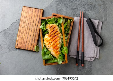 Healthy lunch in wooden Japanese Bento box. Balanced healthy food grilled chicken and avocado with asparagus and green salad.