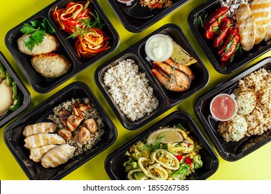 Healthy lunch at the workplace. Pick up food in black containers with Cutlery on a yellow background - Shutterstock ID 1855267585