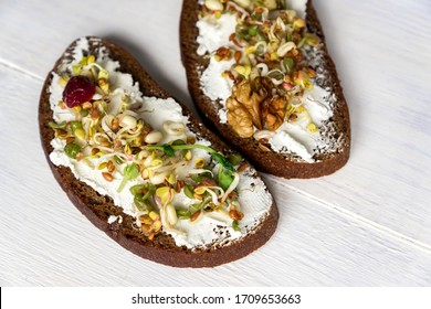 Healthy macrobiotic breakfast. Sandwich with cream cheese, peas microgreens and sprouted mung beans, walnut, sunflower and flax on wooden background. vegan, raw food diet