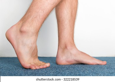 Healthy male feet making a step over home-like background.