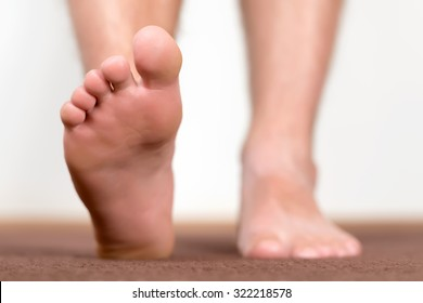 Healthy male feet stepping over home-like background.