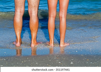 Healthy male and female legs  feet on the sandy shore on the blue sea  background