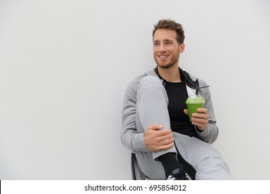 Healthy man drinking green smoothie post workout at gym. Sport athlete with spinach cold pressed juice plastic cup drink relaxing on white background.