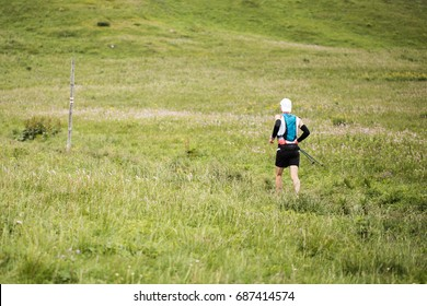 healthy man running outdoors in the mountains on meadow green grass trail