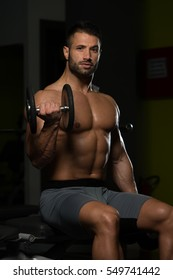 Healthy Man Working Out Biceps In A Dark Gym - Dumbbell Concentration Curls