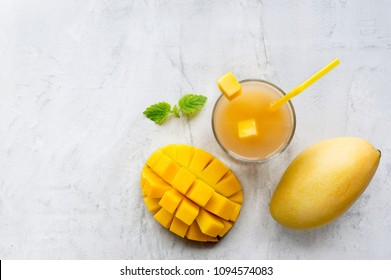 Healthy mango honey smoothie drink in a glass with mint on concrete table. Top view. Copy space.