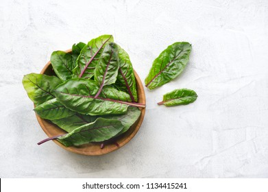 Healthy mangold (beet) green leaves with the red stalk. Top view. Concrete background.